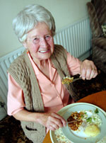 Elderly woman eating dinner
